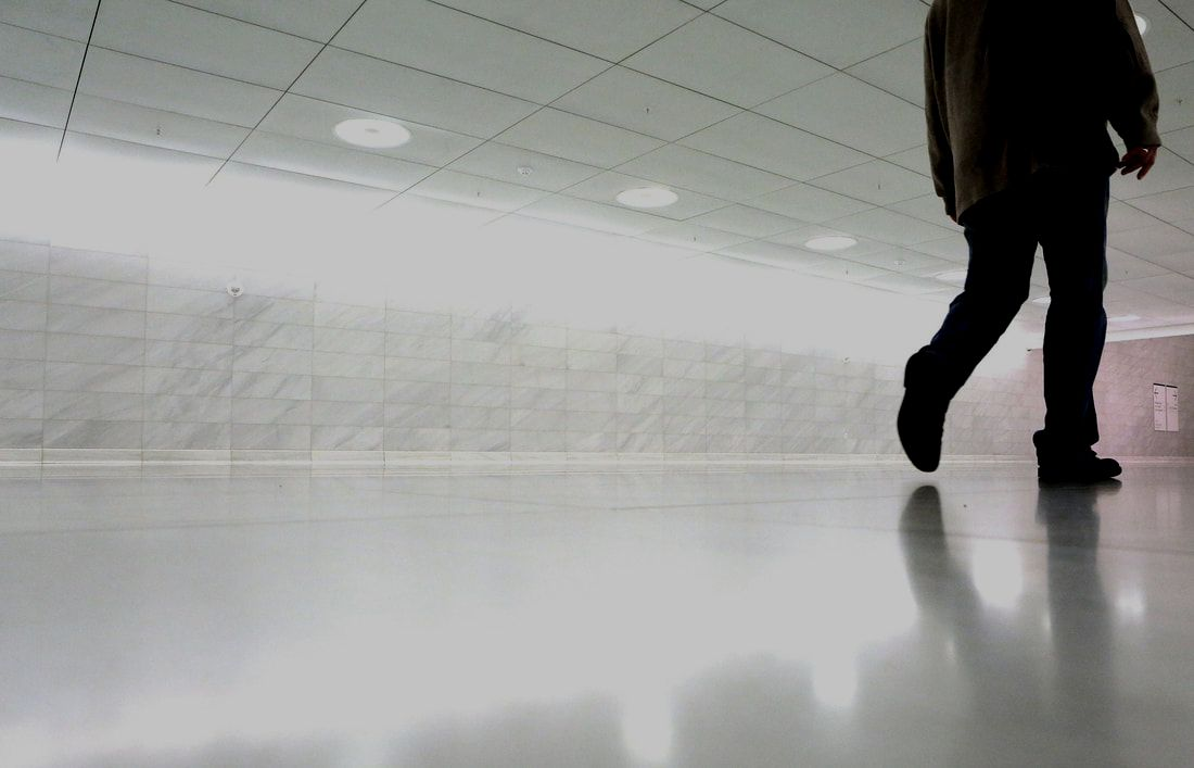 Man wearing dark clothes walking through hallway on bright, white, polished epoxy flooring