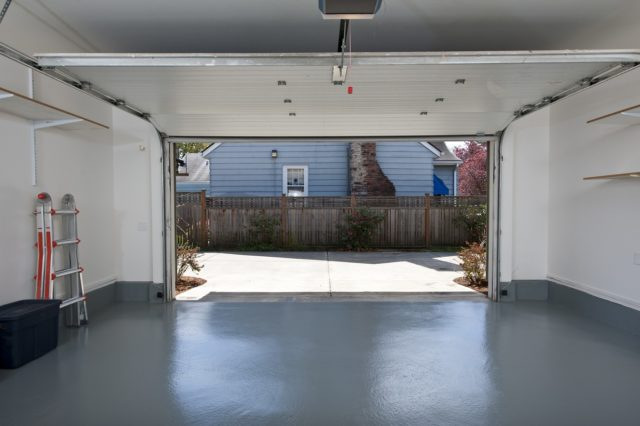 Garage floor covered in epoxy paint with door open showing house next door.